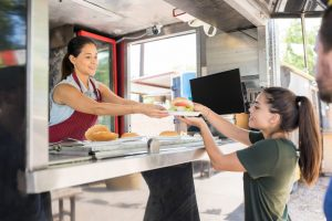 Food truck Catering at a fair in Wesley Chapel, Florida. Photo of a woman serving a girl food out of a food truck.